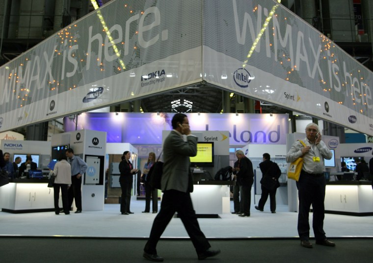 Visitors walk past the WiMAX stand at th