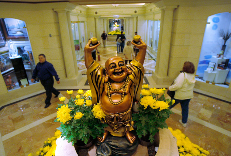 Hotel guests walk past a Buddha statue at the Caesars Palace hotel-casino in Las Vegas.