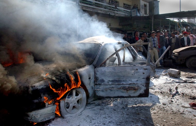 Iraqis gather at a car that caught fire after two bomb blasts in Kirkuk, 180 miles north of Baghdad, Iraq, on Saturday.