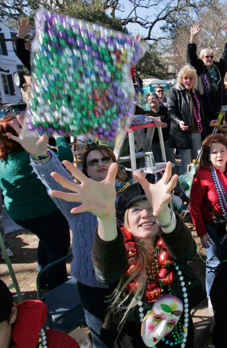 People reach for abag of beadsthrown their way asthe Krewe of Thoth rolls during their Mardi Gras parade through the Uptown area of New Orleans Sunday.