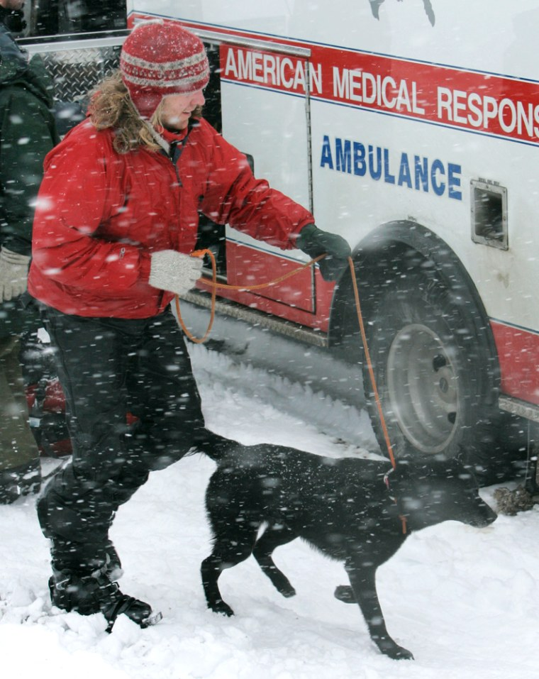 Matty Bryant, 34, of the Portland suburb of Milwaukie, one of the three climbers who were stranded on MountHood since Sunday runs to a waiting ambulance at White River snow park with a black Labrador named Velvet on Monday.