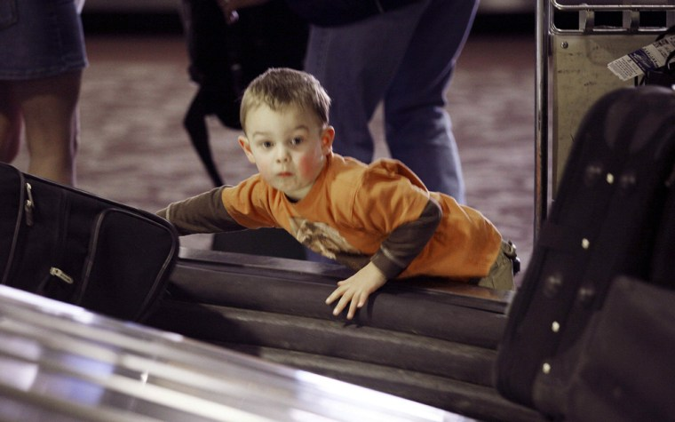 Child looks for luggage in terminal at airport in Phoenix, Arizona