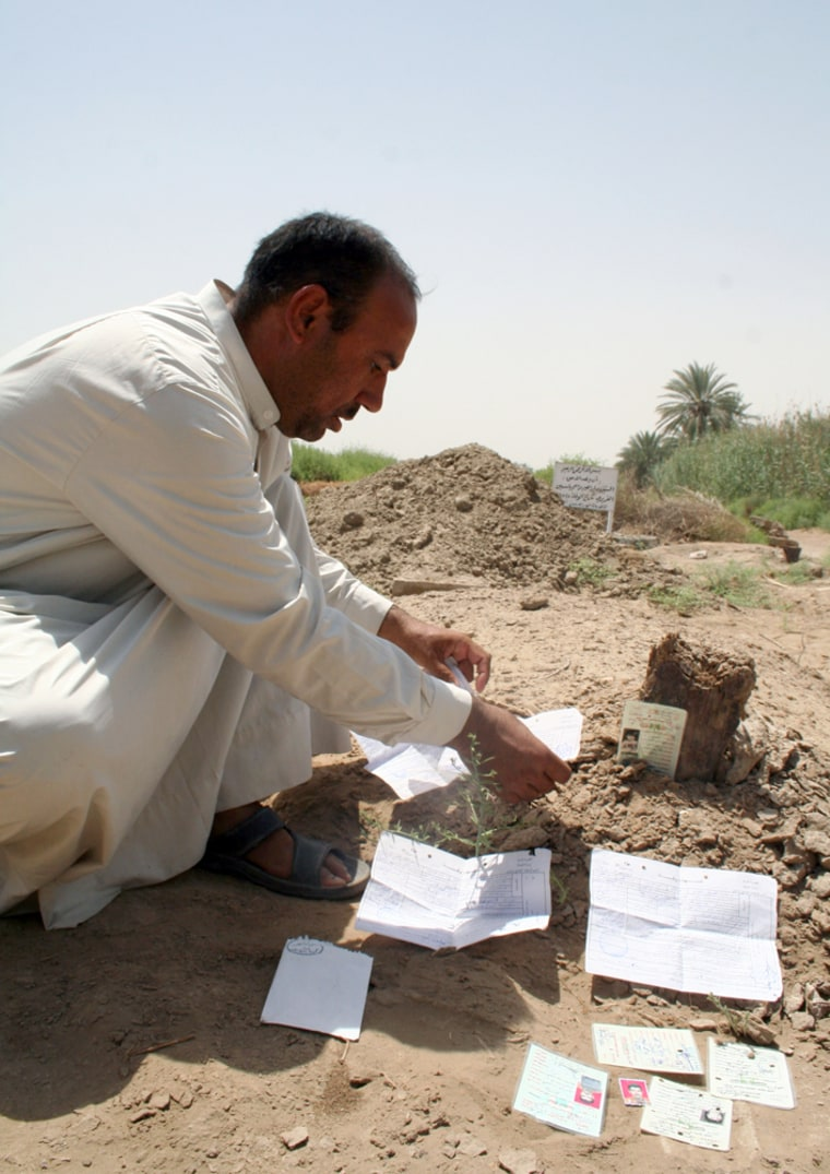 Mohammed al-Janabi, uncle of the girl raped and killed by American soldiers, displays death certificates and IDs on his niece's grave in July 2006 in Mahmoudiya, Iraq.