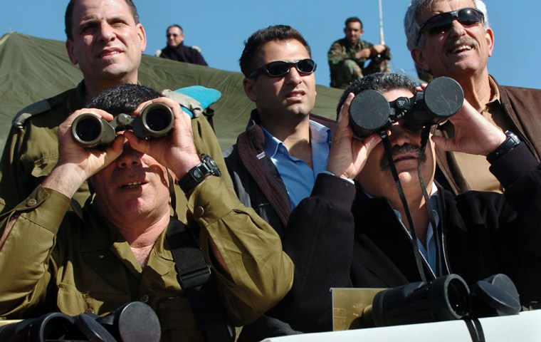 Israeli Defense Minister Amir Peretz, right, gazes at a military drill through binoculars Wednesday, apparentlywithout realizing the lens caps were left on. The army's chief of staff, Lt. Gen. Gabi Ashkenazi is at left.
