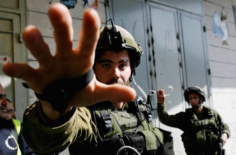 An Israeli soldier gestures towards the camera in Nablus