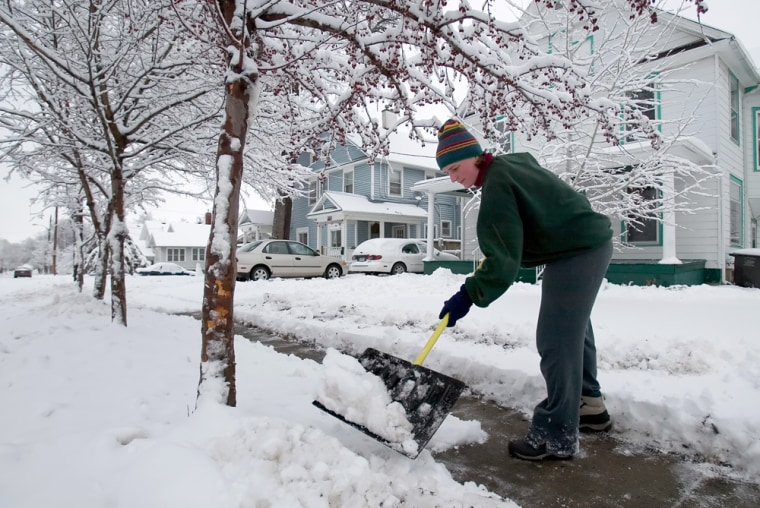 Anna Ryon cleans snow off her sidewalk in Des Moines, Iowa, on Sunday. Hundreds of thousands lost power in Iowa and throughout the Midwest from a major snowstorm.