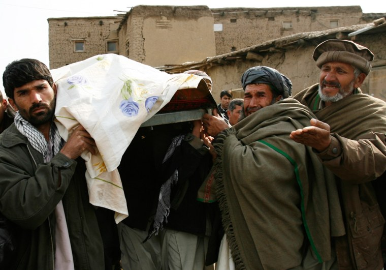 Relatives carry a body after a suicide blast outside the main U.S. military base in Bagram