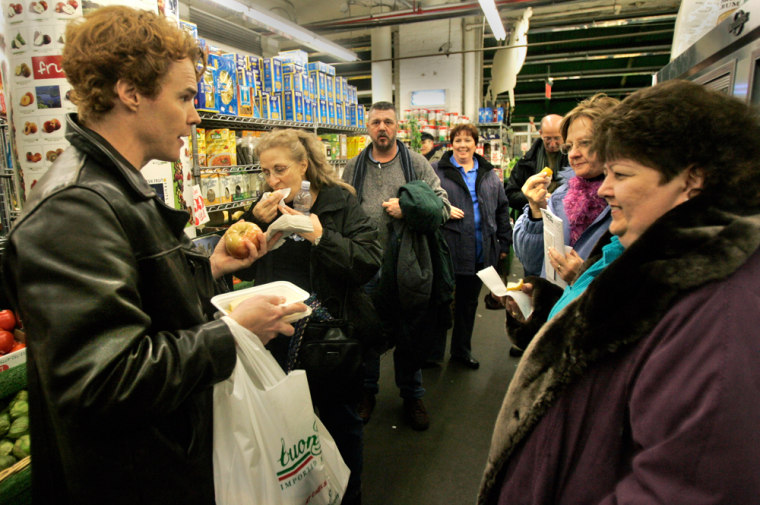 Tour Guide Curt Upton, left, talks to Carol Berger, right, of Delray Beach, Fla. and other tourists at the Chelsea Market in New York. Nationwide, an increasing number of vacationers are basing their travel around food and wine.