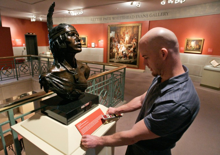Shawn Moore places a plaque on a display of a bust of Pocahontas at the Virginia Historical Society's new exhibit in Richmond, Va. The exhibit takes a look at the traditional view of Pocahontas as well as a new view of her legacy.