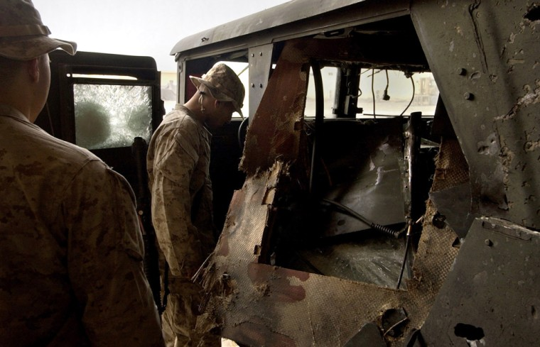 U.S. Marines from the 2nd Battalion, 5th Marine Regiment look over a damaged Humvee at their base after one Marine was killed and three others were injured when the vehicle was struck by a roadside bomb in Ramadi, Iraq, on Oct. 31, 2004.