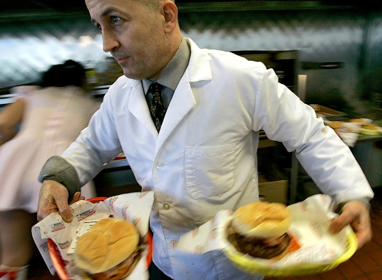 """Jon Basso, owner of the Heart Attack Grill, serves up a pair of """"bypass burgers"""" in hisTempe, Ariz., restaurants."""