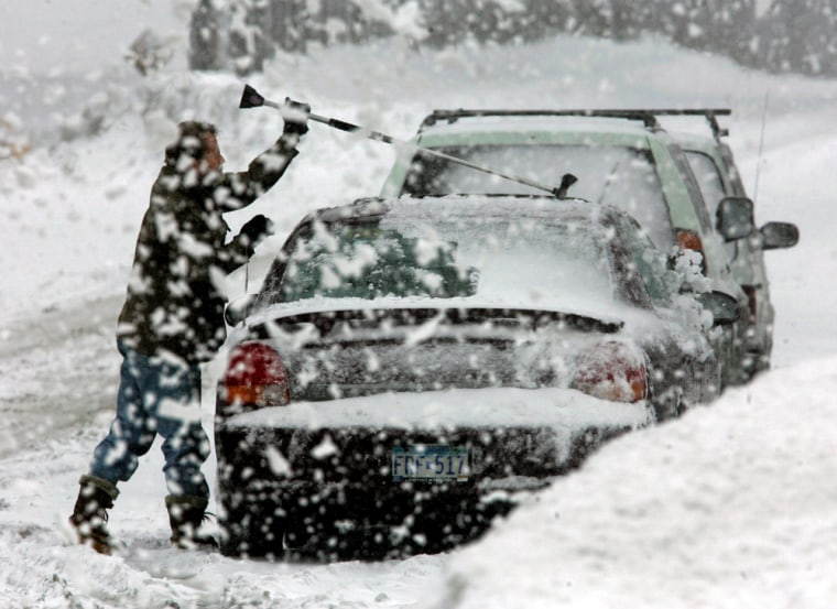 A man clears snow off his car during a winter storm in Minneapolis