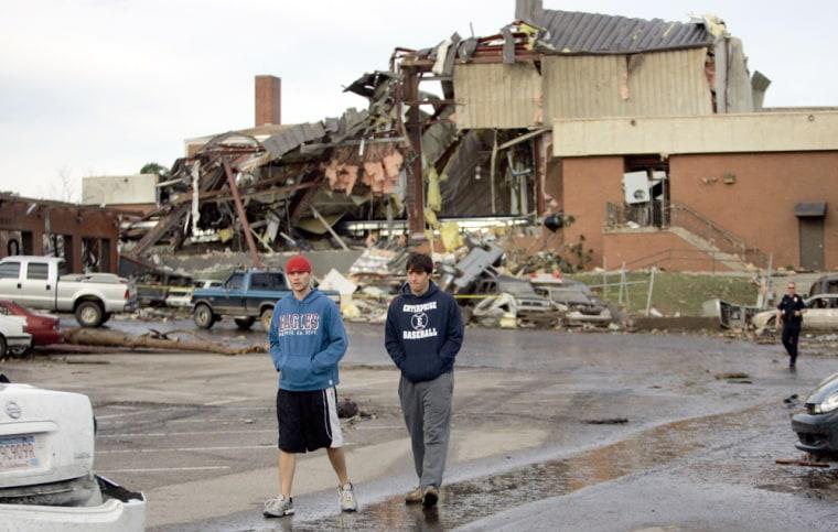 Seniors Ben Sparks, 17, left, and Daniel Carmichael, 18, walk by the tornado-damaged school in Enterprise, Ala., on Friday.