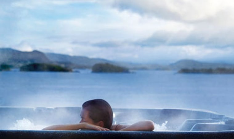 A Solstrand Hotel & Bed guest enjoys an outdoor Jacuzzi overlooking the fjords.