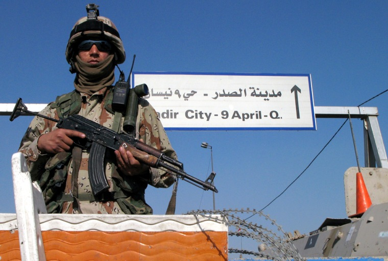 An Iraqi army soldier stands guard at a checkpoint at the entrance to Baghdad's Shiite enclave of Sadr City, IraqonSunday.