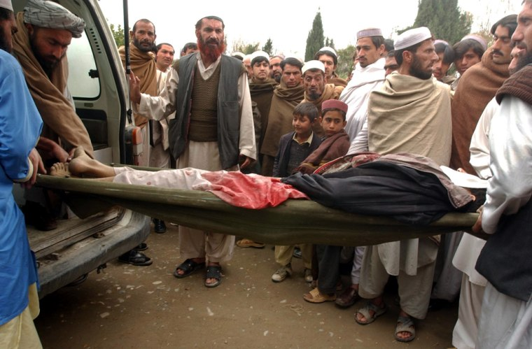 Afghan men carry the body of a civilian they said was killed by Marines after a car bomber attacked their convoy in Nangarhar province on March 4, 2007.