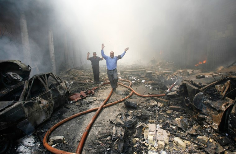 Police officer and fireman scream for rescuers after finding a body at the site of a car bomb attack in Baghdad