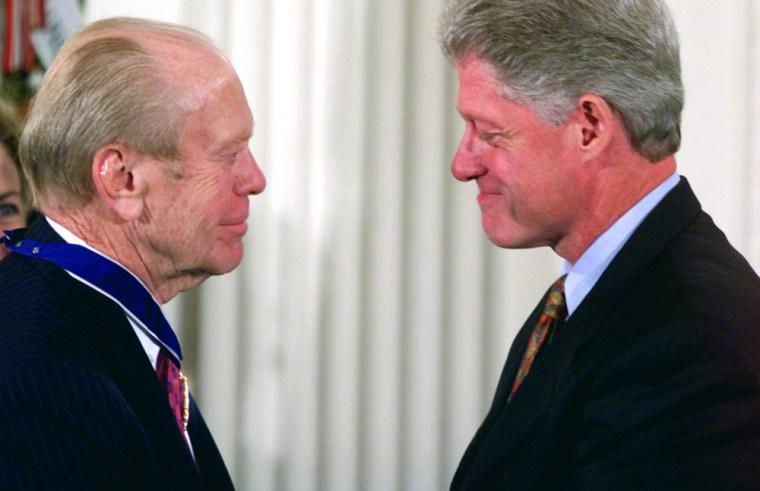 US president Bill Clinton (R) presents former US P