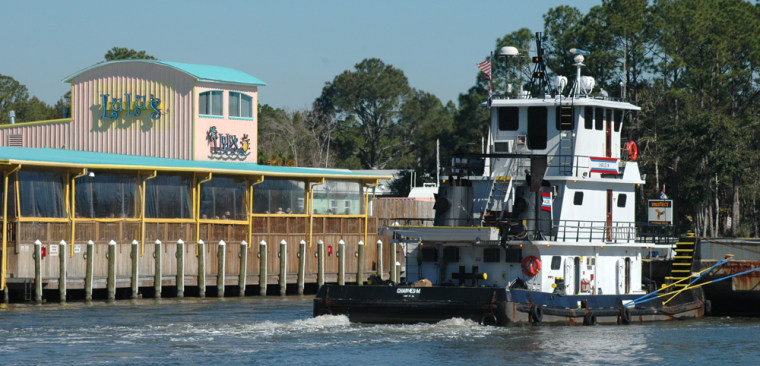 A tug boat pushes a barge as it goes past Lulu's at Homeport Marina, in Orange Beach, Ala. Lulu's, the bar and restaurant run by singer Jimmy Buffett's sister, Lucy, also draws large crowds on the Intracoastal Waterway in Gulf Shores. The Wharf, a major new attraction, offers shopping and entertainment, including, movies and concerts.