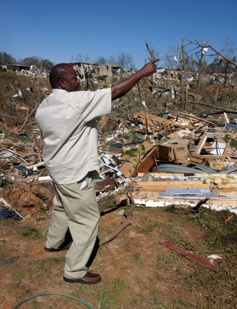 Gary Merritt, 41, stands on the edge of a 20-foot-deep ditch on Monday in Americus, Ga., showing how high his house was lifted by a tornado last week.