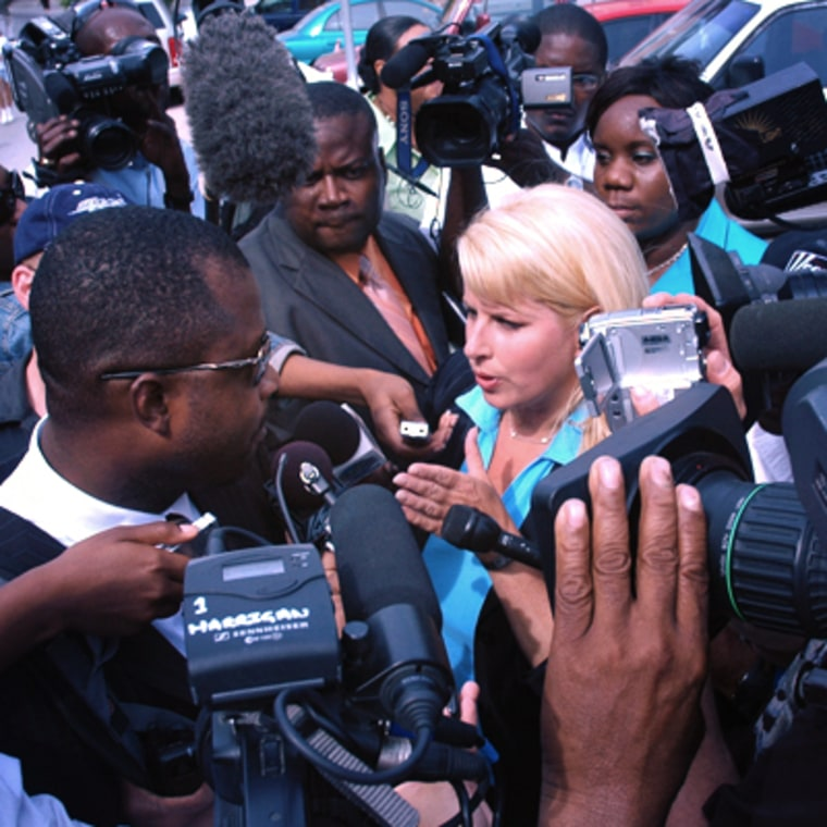 Rita Cosby and a throng of reporters fight for an interview outside the courthouse in the Bahamas.