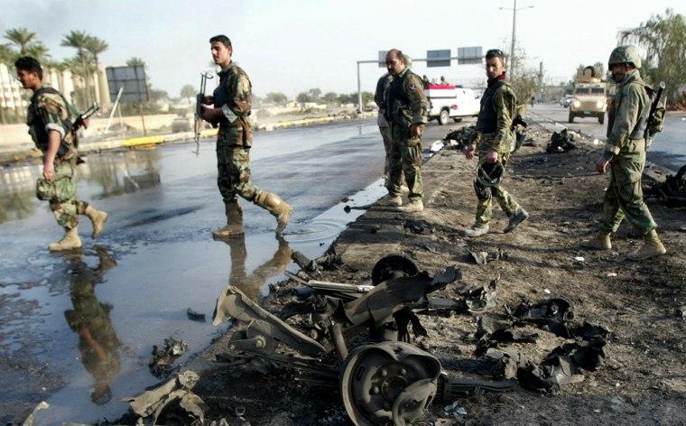 Iraqi army soldiers walk past car wrecka