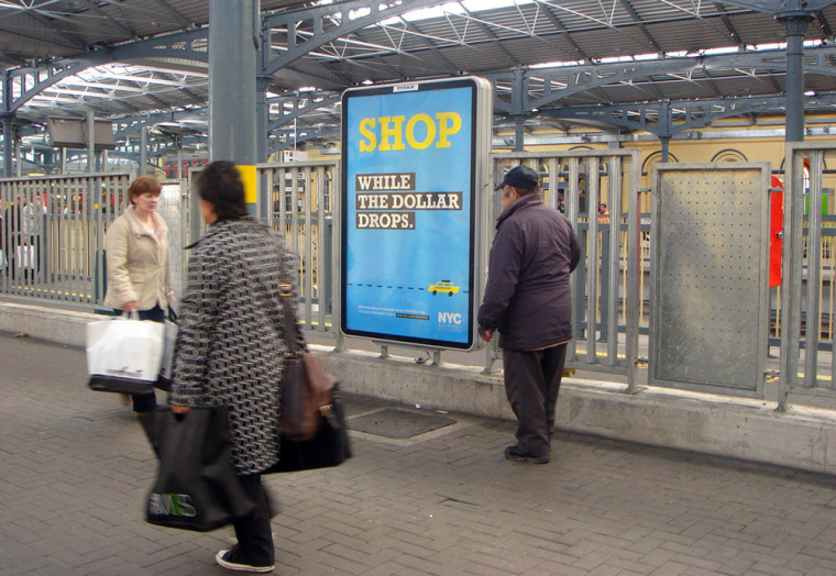 people cross in front of an advertisement promoting New York City tourism at a rail station in Dublin, Ireland. The advertisement is a component of an ambitious campaign designed to promote New York City around the globe.