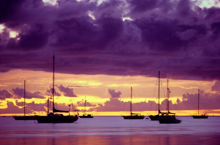Sailboats anchored at sunset, in Papeete, Tahiti.