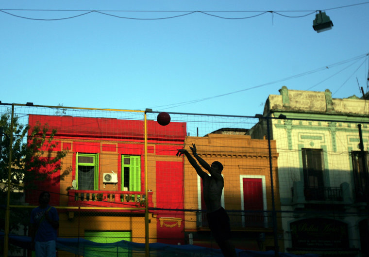 Back dropped by colorful painted immigrant homes, a man plays with a ball in the Buenos Aires tourist district of La Boca, which is world-famous for being the cradle of the melancholic tango music and of Boca Juniors soccer team.