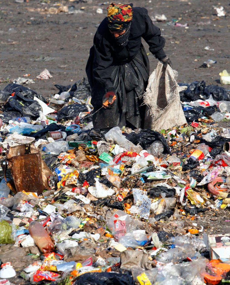 A woman picks through garbage at a garbage dump in Baghdad's Sadr city