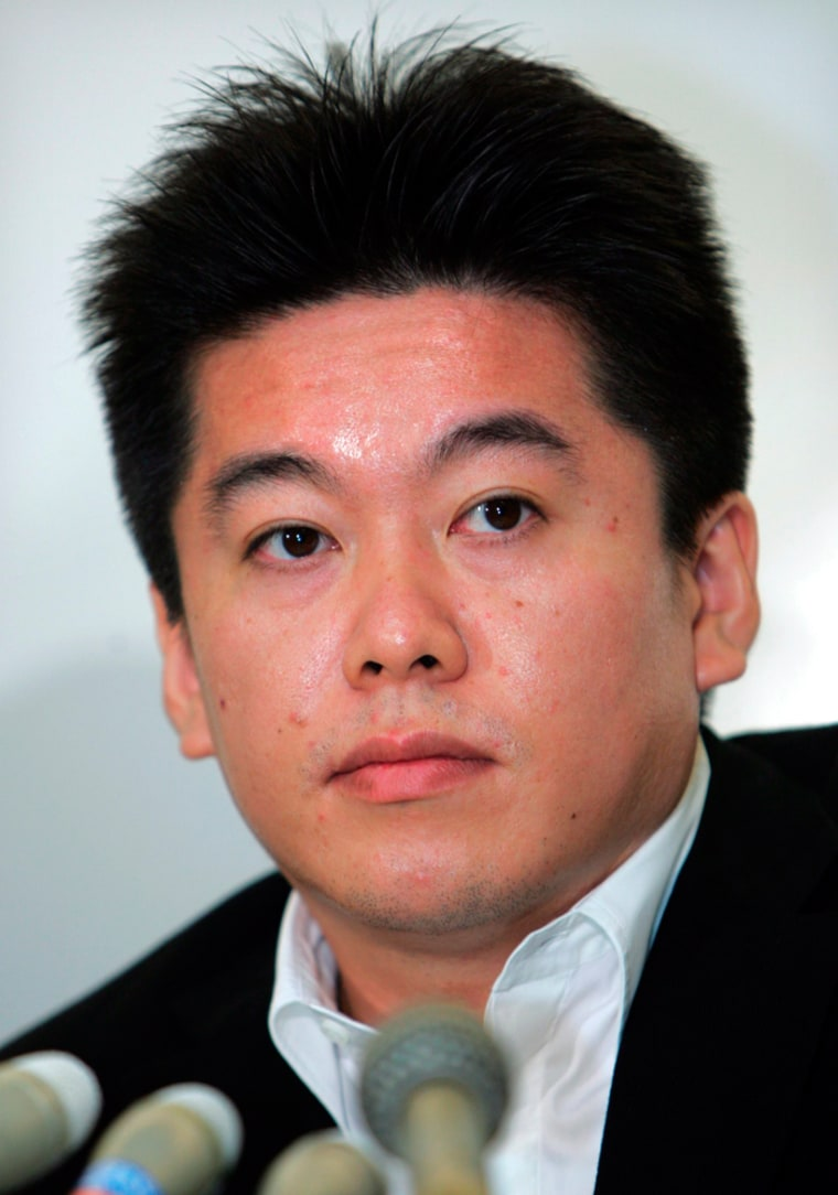File photo of Takafumi listening to a journalist at a news conference in Tokyo