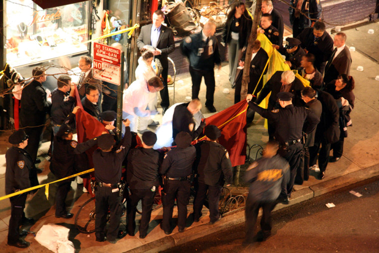 Policemen gather around thebody of the gunman in New York's Greenwich Village on Wednesday night after he shot and killed a pizza parlor employee and two unarmed volunteer police officers who pursued him. The gunman was then shot to death by other police officers.