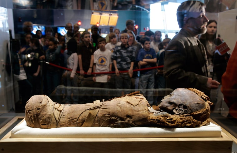 Charles F. Hildebolt, right, a dentist and anthropologist at Washington University, talks about the research he helped conduct on a baby mummy as it sits on display at the St. Louis Science Center.