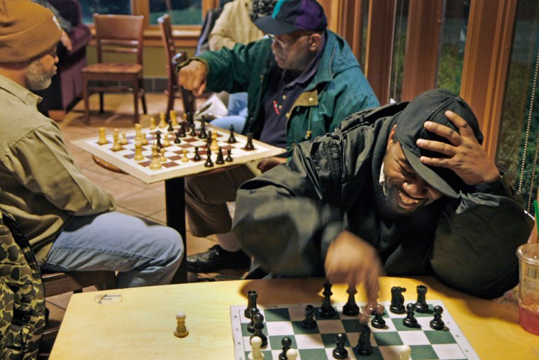 Frank Evans, bottom right, taunts his opponent as he wins game after game of chess on Feb. 2 at the Starbucks outlet in Forestville, Md. He's one of the black men in the areaputting a singular African American spin on a game considered mainly European in appeal.