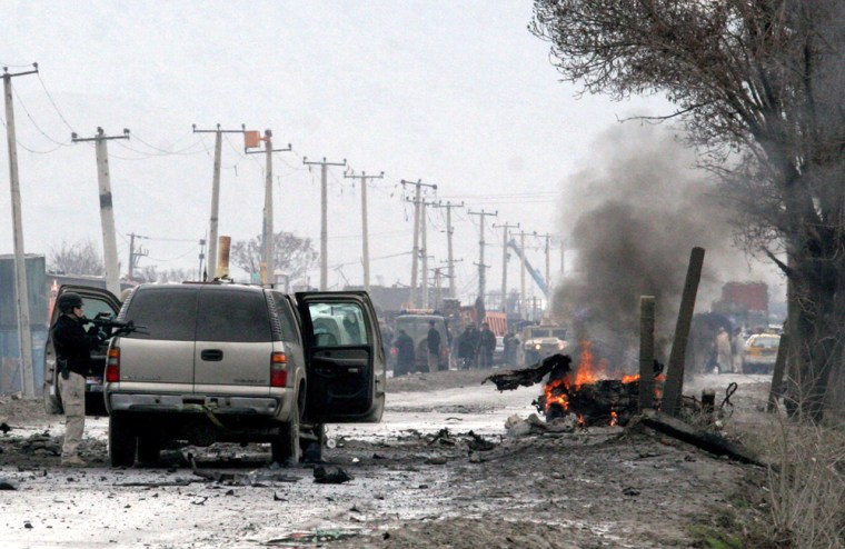 A U.S. security guard stands near the still burning vehicle of a suicide attacker in Kabul, Afghanistan, on Monday. The car bomb exploded next to a U.S. Embassy convoy, pushing an embassy SUV across the road and setting it on fire, officials said.