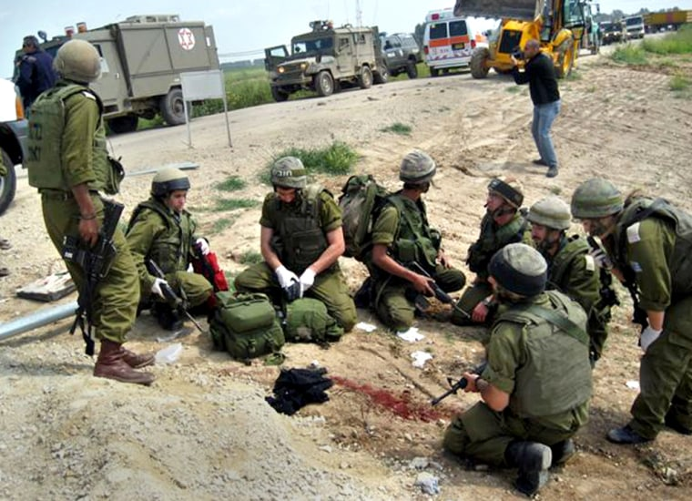 Israeli soldiers gather Monday around a blood stain on the ground after an attack by Palestinian militants just outside the Gaza Strip.