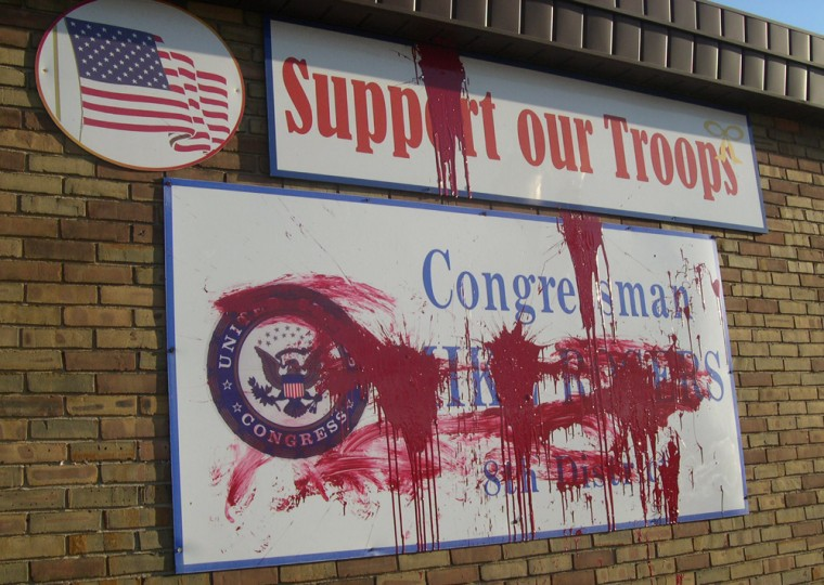 In this photo provided by U.S. Rep. Mike Rogers' office, splattered red paint covers signs at Rogers' Lansing, Mich., office on Tuesday.