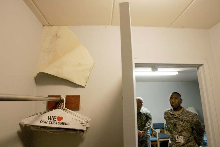 Army Master Sgt. Gary Rhett, building manager, looks last Thursday at a section of wallpaper that was pulled back to reveal mold in a room in the Walter Reed Army Medical Center, which was used to house recovering wounded soldiers.