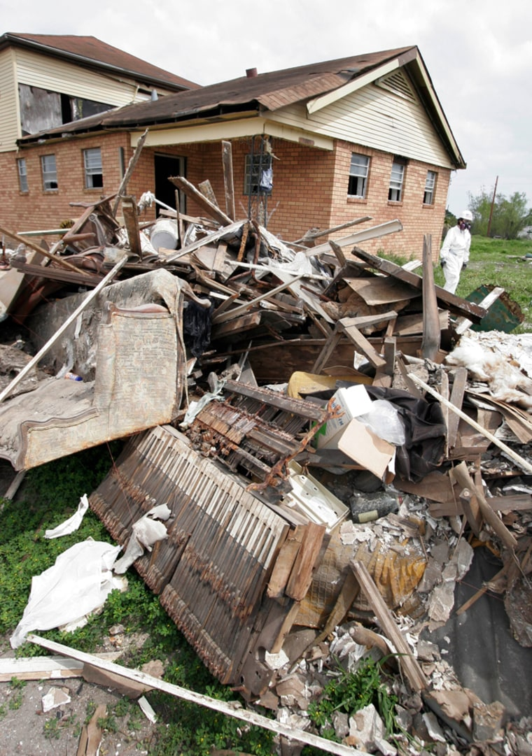Debris piles up outsidea house in the Lower Ninth Ward of New Orleans on Wednesday as volunteers help gut the structure. The area has been slow to repopulate since Katrina hit.