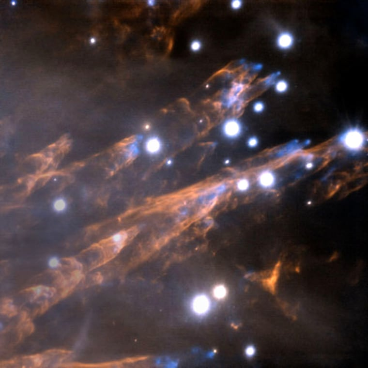 """This composite image at infrared wavelengths shows the Orion """"bullets"""" as blue features and represents the light emitted by hot iron gas. The light from the wakes, shown in orange, is from excited hydrogen gas."""