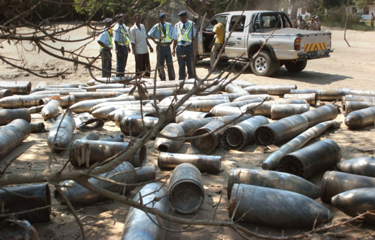 Police officers inspect artillery shells Friday after an explosion Thursday night at a weapons depot in Maputo, Mozambique.