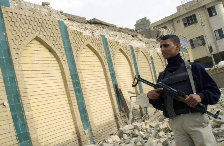 Iraqi soldier stands guard outside a destroyed Sunni mosque after a bomb attack in Haswa
