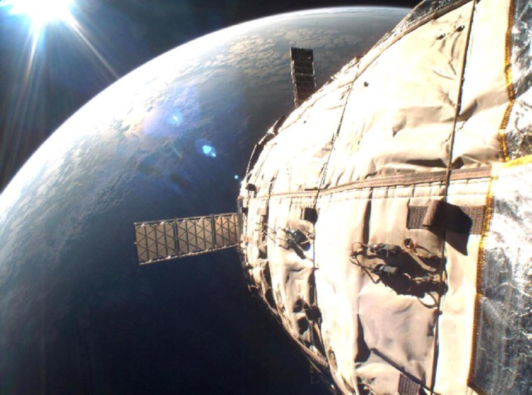 Earth takes on a golden lining in this March 20 picture, snapped by a camera aboard Bigelow Aerospace's Genesis 1 orbital module. Genesis 1's hull and solar panels arevisible in the foreground.