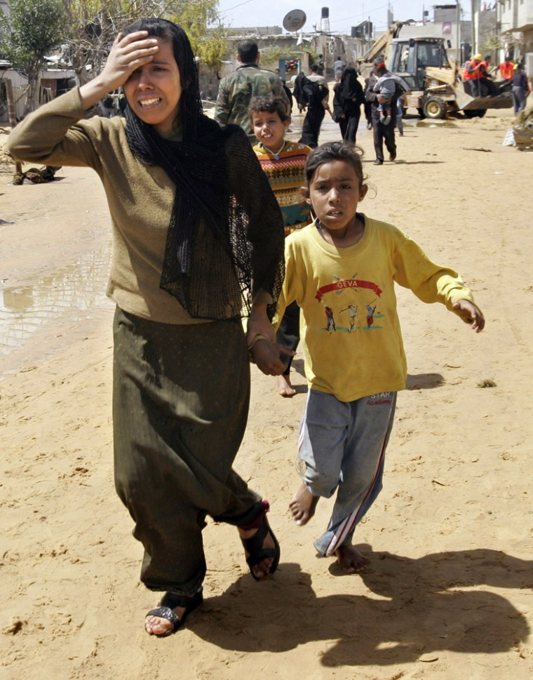 Palestinians run from the scene of a sewage flood in the village of Umm Naser, in the northern Gaza Strip, on Tuesday.