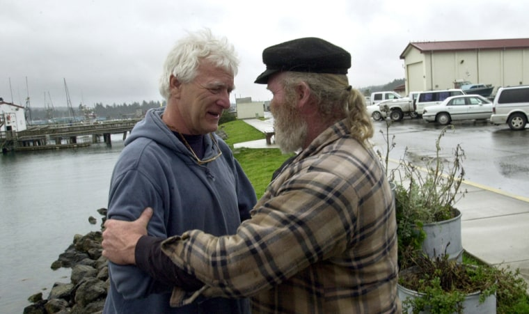 Dave Sharp, right, talks withDon Yost, who quit his job as harbormaster rather than impound the boats of salmon fishermen who have fallen months behind in paying their mooring fees, on March 19 in Coos Bay, Ore.