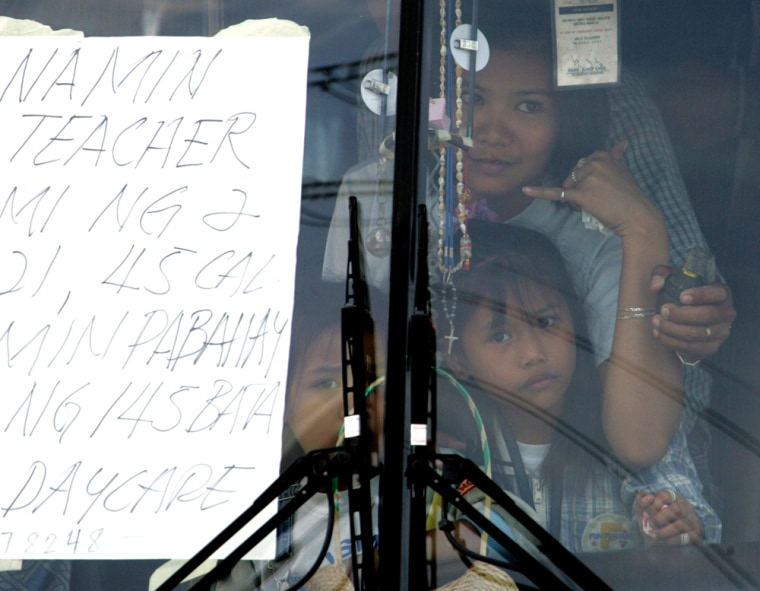 A hostage gestures for a phone Wednesday as a grenade is held near her by Jun Ducat inside a tourist bus outside City Hallin Manila, Philippines. Ducat is charged with hijacking a busload of students and teachers, and driving them to the site to demand better housing and education for the children.He was later arrested.