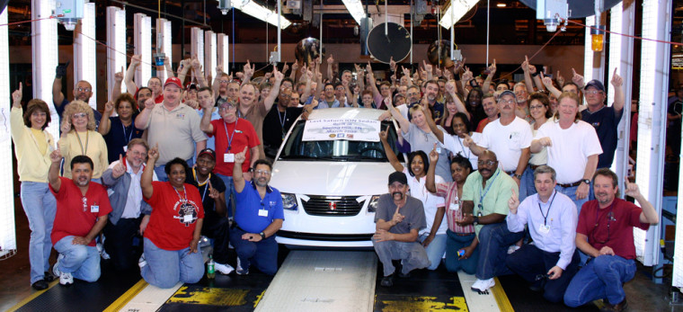 Workers surround the last Saturn Ion sedan that rolled off the line at the Saturn plant in Spring Hill, Tenn.