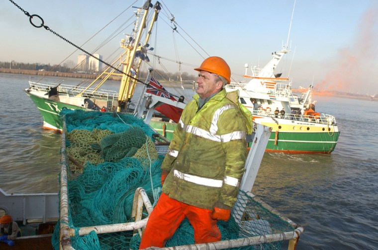 ** ADVANCE FOR SUNDAY, APRIL 1 ** FILE ** A fisherman stands on a basket of nets aboard his ship as a group of North Sea fishing boats pull in to anchor in the Port of Antwerp, Belgium, Dec. 10, 2003. North Sea fisherman gathered in Antwerp to protest proposed EU cuts on commercial catches of cod, hake and other dwindling varieties. Overfishing has cut deeply into the North Sea's cod population in recent decades, and scientists now say this important food fish faces a second challenge _ climate change. (AP Photo/Virginia Mayo)