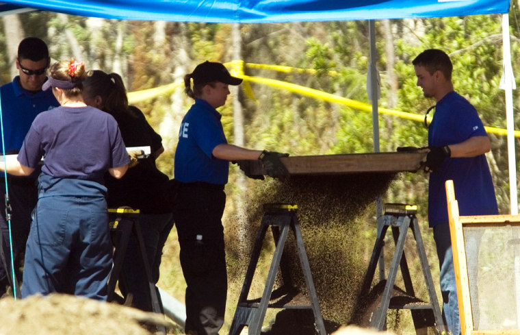 Investigators with the Florida Department of Law Enforcement and the Fort Myers Police Department sift through dirt Monday at the site where eight skeletons were found.
