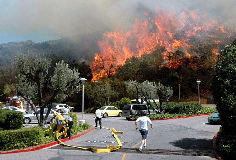 Residents run for their cars in a parking lot behind the Oakwood Apartments as a wildfire burns in the Hollywood Hills section of Los Angeles on Friday.
